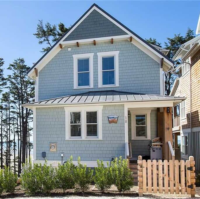 blue beach house with wood picket fence