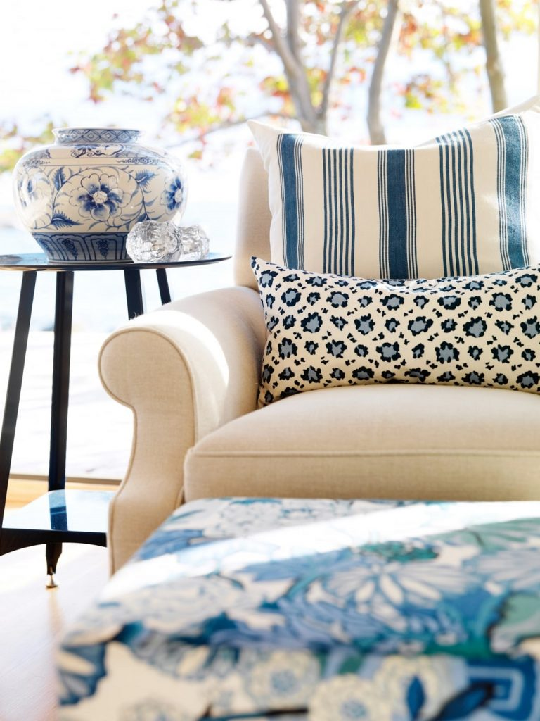cream chair with blue and white pillows